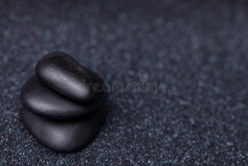 Balansera fridsamma svarta stenar i den avslappnande zenen arbeta i trädgården royaltyfri fotografi