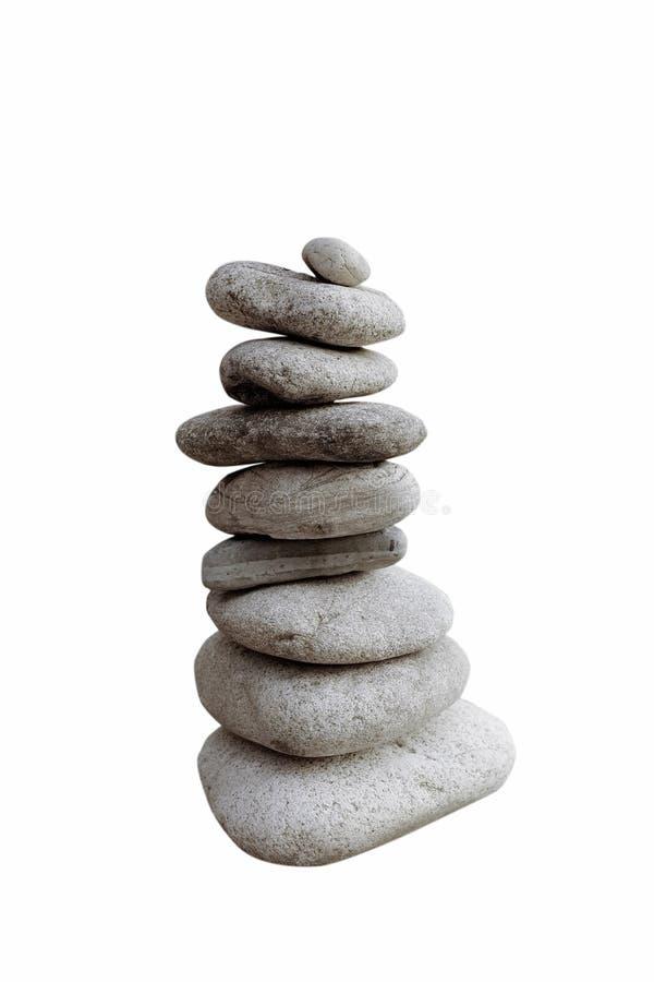 Balansera stenar som isoleras på vit bakgrund arkivfoton