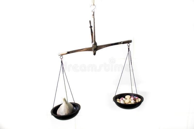 Balansowa skala z pigułkami i czosnkiem zdjęcie stock
