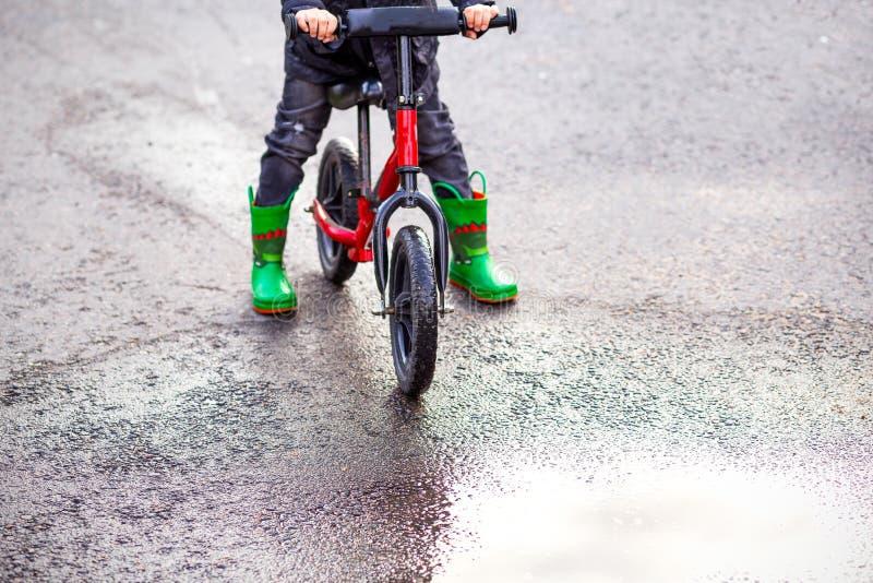 Balansowy rower, Zieleni gumowi buty i kałuża Dzieciństwo fotografia royalty free