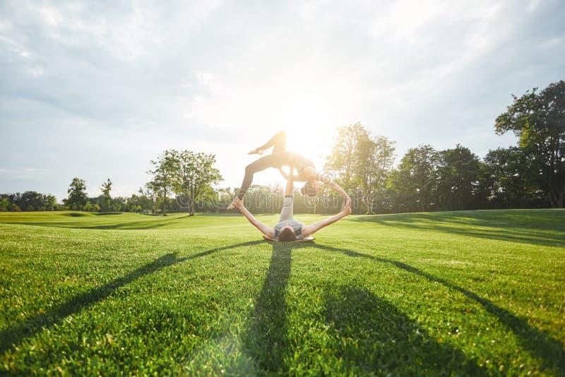 Balanza de Acro Pares jovenes y sanos que practican yoga acrobática en campo abierto en una mañana soleada Hombre deportivo que m foto de archivo libre de regalías