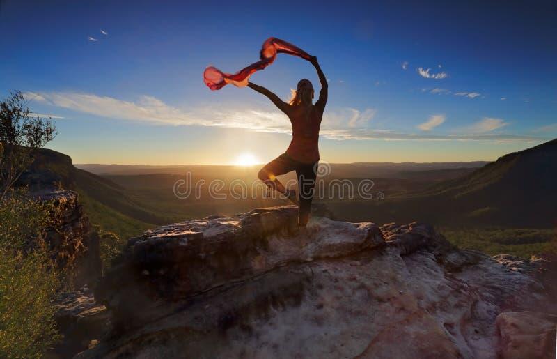 Balanza de la yoga de Pilates de la mujer con la tela que fluye escarpada foto de archivo