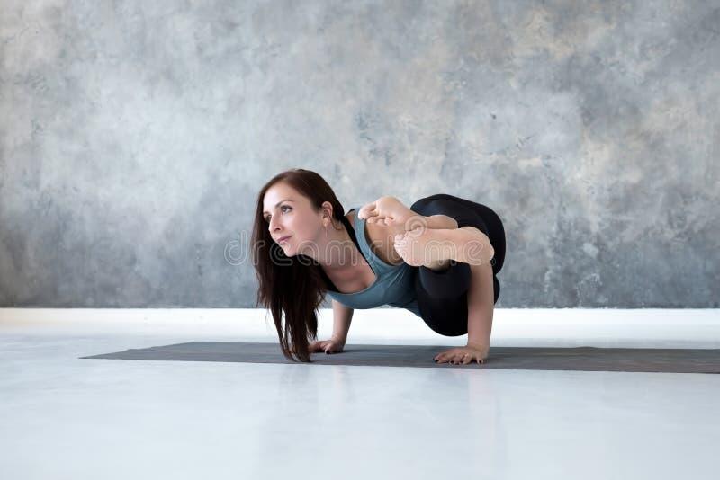 Balanza del brazo de la tenencia de la mujer joven en actitud de la yoga de Astavakrasana fotografía de archivo