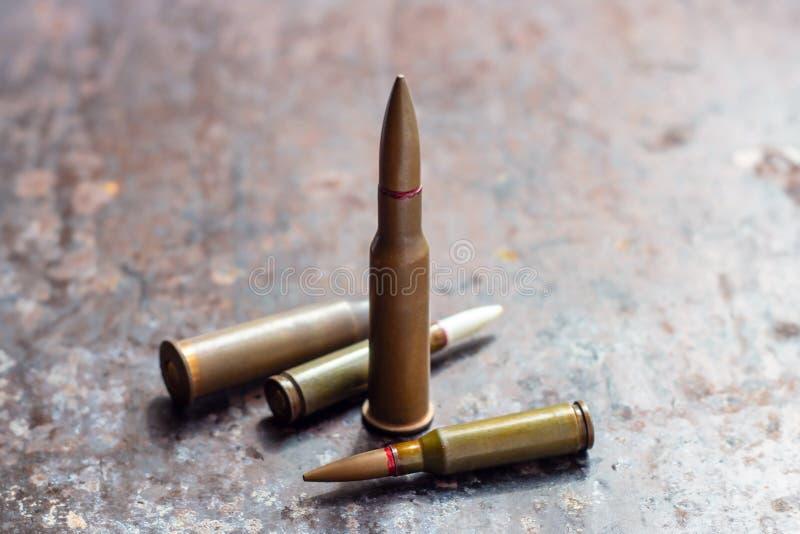 Balas del arma en fondo oxidado del metal Industria militar, guerra, comercio de armas global y concepto del crimen foto de archivo