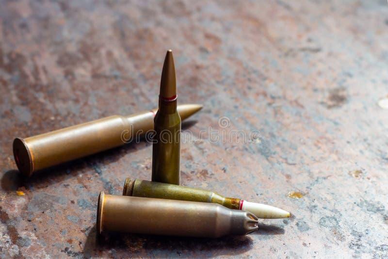 Balas del arma en fondo oxidado del metal Industria militar, guerra, comercio de armas global y concepto del crimen imagen de archivo