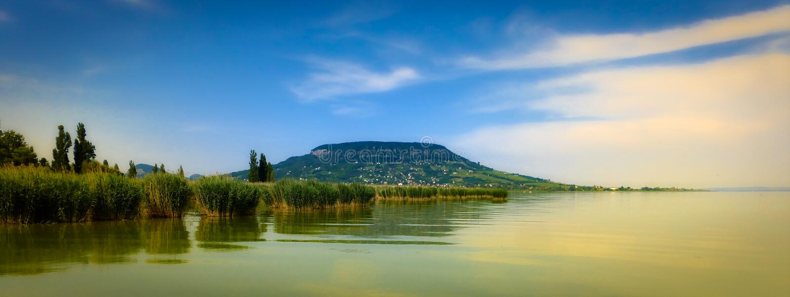 Balaton lake and a hill in the background. The Balaton lake in Hungary and a hill in the background, calm water, blue sky with smooth high-level clouds stock photo