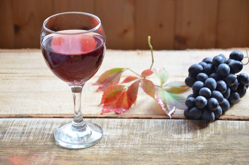 Balayez les raisins noirs sur la surface en bois, copiez l'espace Vin rouge et raisins Vin et raisins dans l'arrangement de vinta photos libres de droits