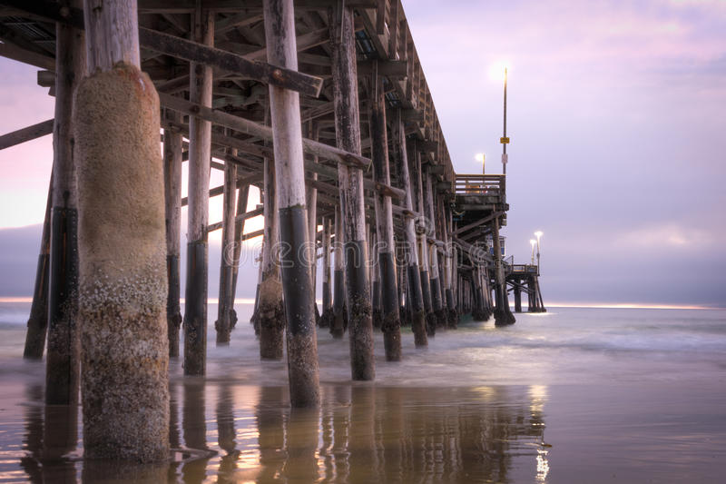 Balboa Pier Newport Beach. Long exposure captures slow moving waves under The Balboa Pier in scenic Newport Beach, California royalty free stock image