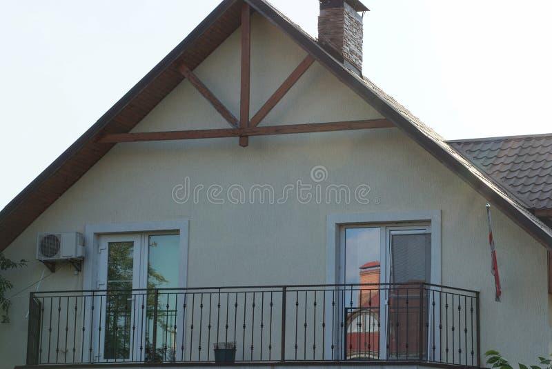 Balcão aberto preto do ferro na fachada de uma casa marrom com uma janela fotos de stock