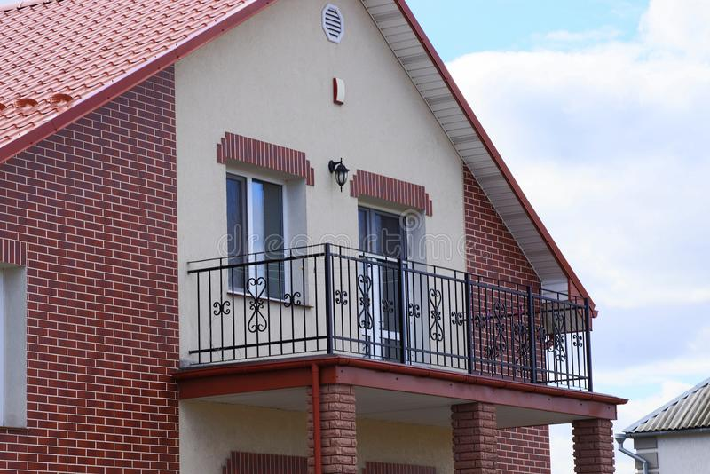Balcão aberto preto do ferro na fachada de uma casa marrom do tijolo com uma janela e uma porta foto de stock royalty free