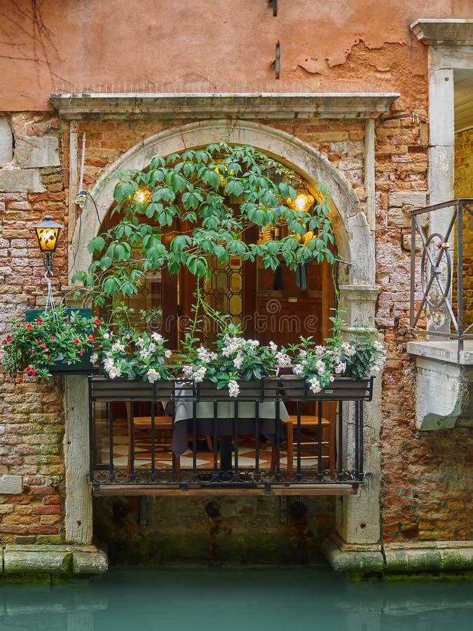 Balcão arqueado velho com flores, Veneza, Itália imagens de stock royalty free