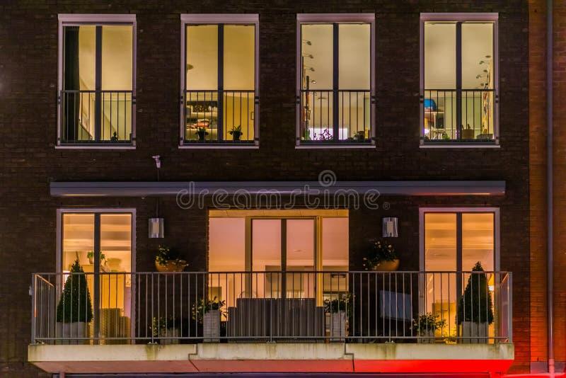 Balcão bonito do apartamento decorado com plantas, janelas iluminadas na noite, arquitetura holandesa moderna fotografia de stock royalty free