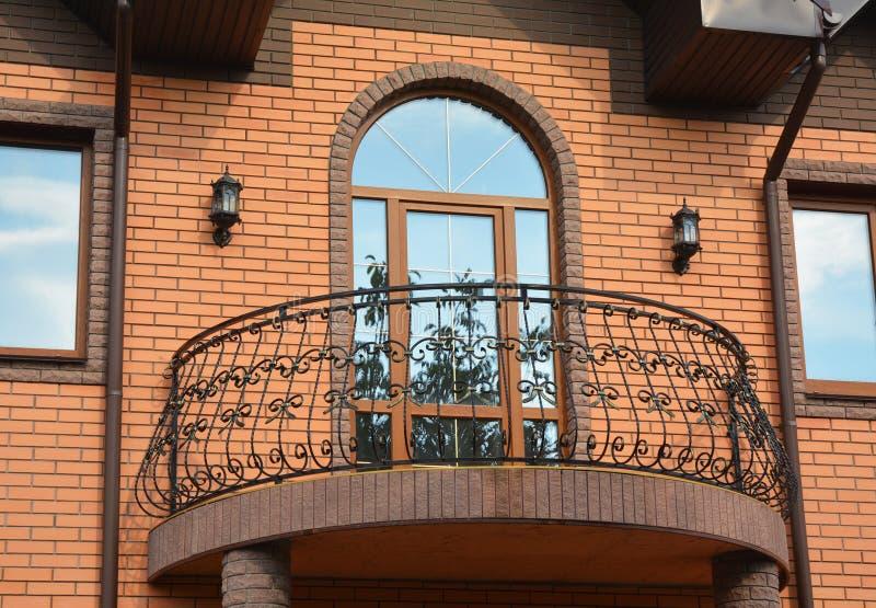 Balcão bonito do metal no exterior da casa do tijolo fotografia de stock royalty free