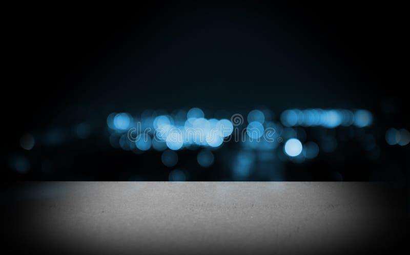 Balcão branco do tampo da mesa da etapa vazia na construção da opinião da arquitetura da cidade do borrão na noite imagem de stock
