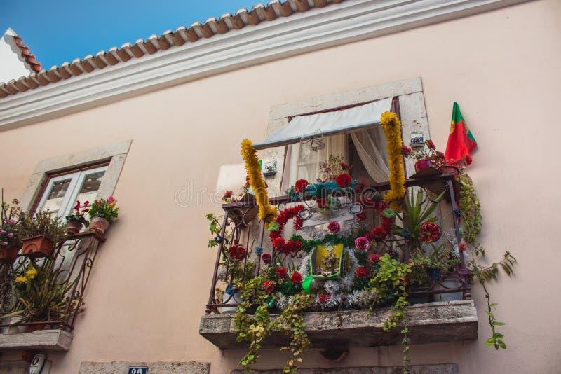Balcão com bandeira portuguesa e flores em Lisboa, Portugal Decoração exterior urbana Conceito da decoração dos balcões fotografia de stock royalty free