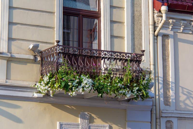 Balcão com flores e os trilhos dados forma do ferro forjado fotos de stock royalty free