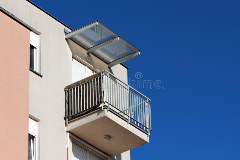 Balc?o de canto do pr?dio de apartamentos moderno cercado com a cerca de seguran?a cinzenta do metal e as cortinas de janela fech foto de stock