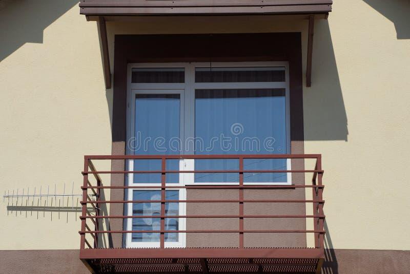 Balcão marrom aberto com janela e porta na parede da casa imagem de stock royalty free