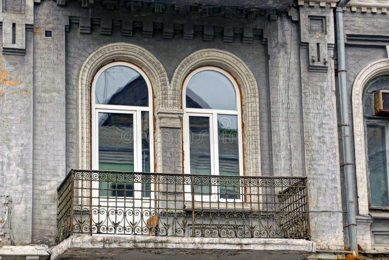Balcón abierto del hierro viejo en una pared con una puerta de cristal y una ventana foto de archivo