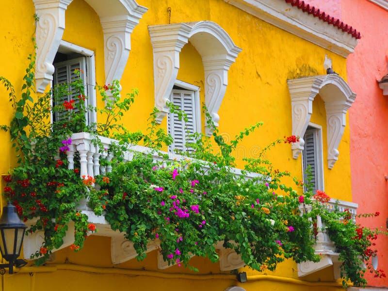 Balcón amarillo con las flores imagenes de archivo