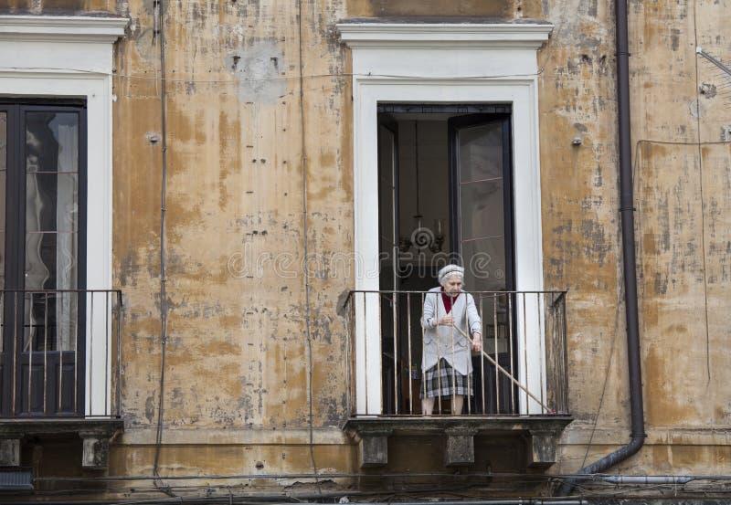 Balcón arrebatador de la vieja señora italiana Catania, Sicilia Italia fotos de archivo libres de regalías