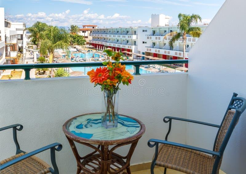Balcón con las sillas y piscina de desatención de la tabla en el centro turístico tropical de lujo del hotel fotografía de archivo libre de regalías