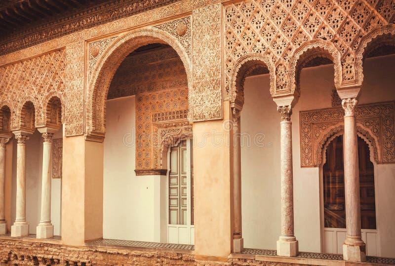 Balcón con las tallas y los arcos dentro del palacio real del Alcazar del siglo XIV, estilo mudéjar de la arquitectura, Sevilla fotografía de archivo