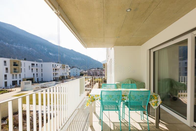 Balcón con los muebles al aire libre, día soleado imagen de archivo