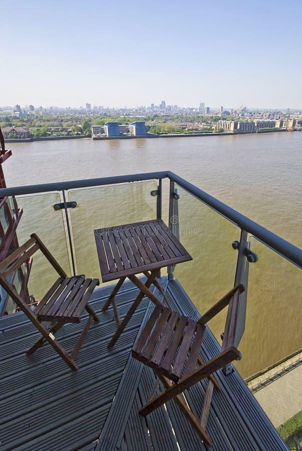 Balcón con opiniones al aire libre de los muebles y del río fotografía de archivo