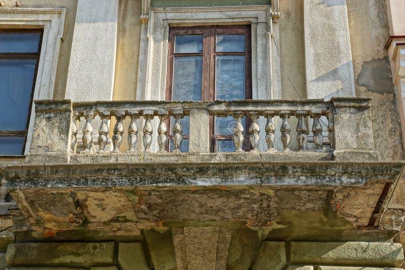 Balcón concreto abierto gris retro en la pared vieja sucia con la ventana imágenes de archivo libres de regalías