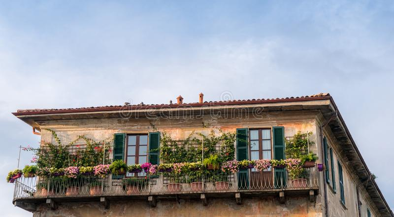 Balcón en chalet italiano con las flores hermosas y coloridas fotos de archivo