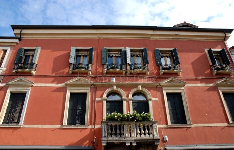 Balcón florecido rojo del palacio con diez ventanas y dos puertas de cristal en Monselice en el Véneto (Italia) imagen de archivo libre de regalías