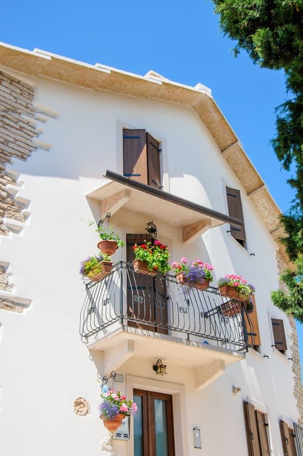 Balcón hermoso del vintage con las flores coloridas y las puertas de madera foto de archivo libre de regalías