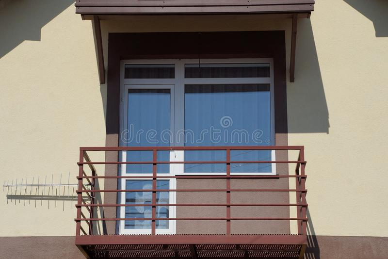 Balcón marrón abierto con la ventana y puerta en la pared de la casa imagen de archivo libre de regalías