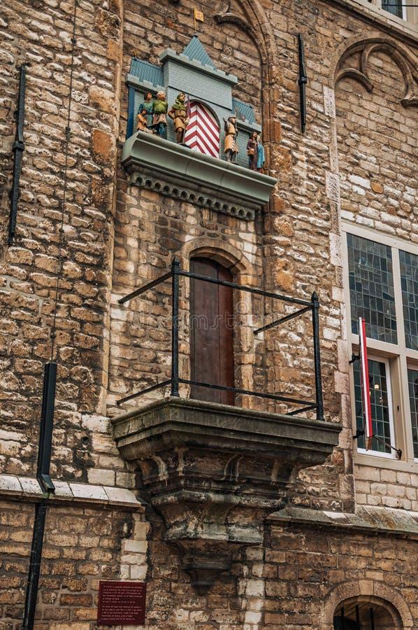 Balcón y carillón con las marionetas mecánicas al lado del edificio gótico de ayuntamiento del Gouda en un día nublado imagenes de archivo
