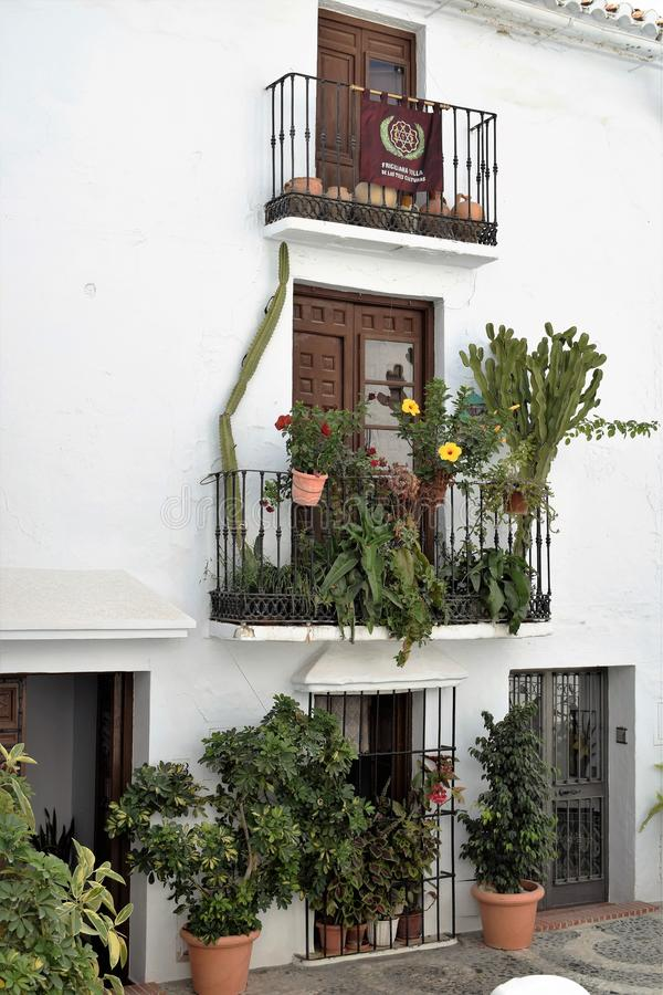 Balcões encantadores decorados com plantas e potenciômetros em Frigiliana, vila branca espanhola a Andaluzia fotos de stock