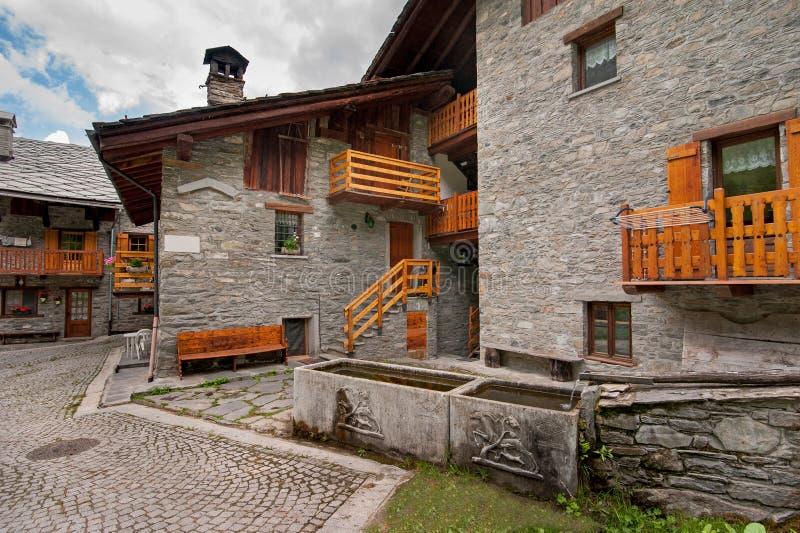 Balcões nas casas alpinas da pedra da rua da vila fotos de stock