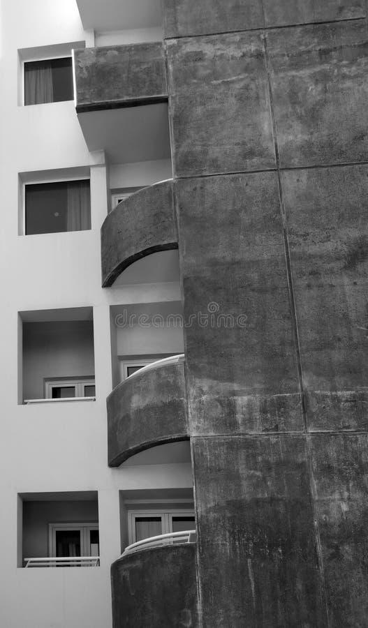 Balc?es curvados e janelas quadradas em um pr?dio de apartamentos concreto manchado velho imagem de stock
