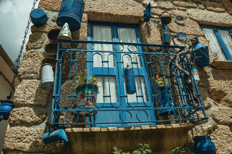 Balc?o decorado com lotes de bandejas azuis na fachada de pedra da casa foto de stock