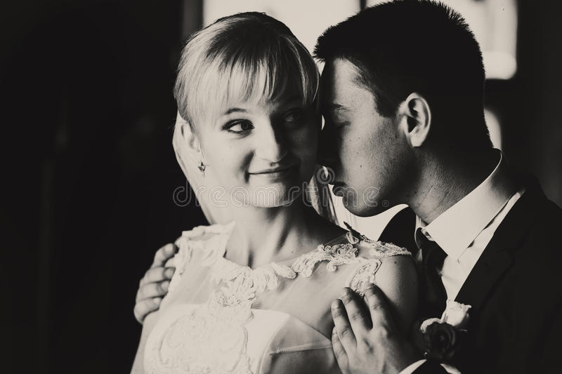 A balck and white picture of smiling bride and groom holding her. Shoulders tenderly royalty free stock photo