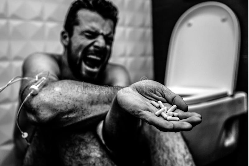 Balck and white picture of young man screaming and yelling on floor in rest room. He suffer. Guy show pills in hand royalty free stock photography