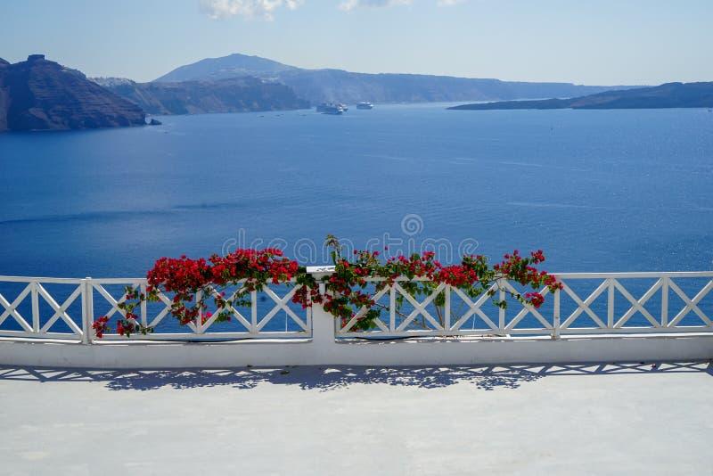 Balcon blanc d'île avec le premier plan rouge-rose foncé de fleur de bouganvillée devant la vue scénique et la caldeira de la mer photo stock
