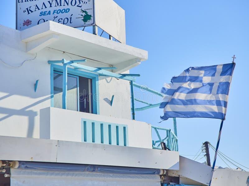Balcon bleu d'une taverne grecque avec une ondulation de drapeau Kos, sud EA photos stock