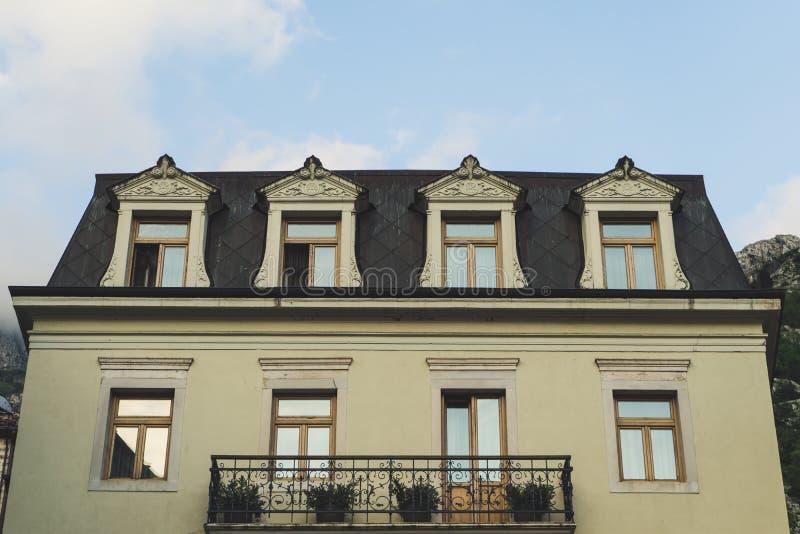 Balcon europ?en traditionnel avec les fleurs et les pots de fleurs color?s Bâtiment de modèle jaune avec les fenêtres en bois et  photographie stock libre de droits