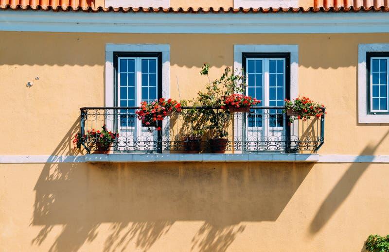 Balcon symétrique avec des fleurs avec la façade jaune de peinture photos libres de droits