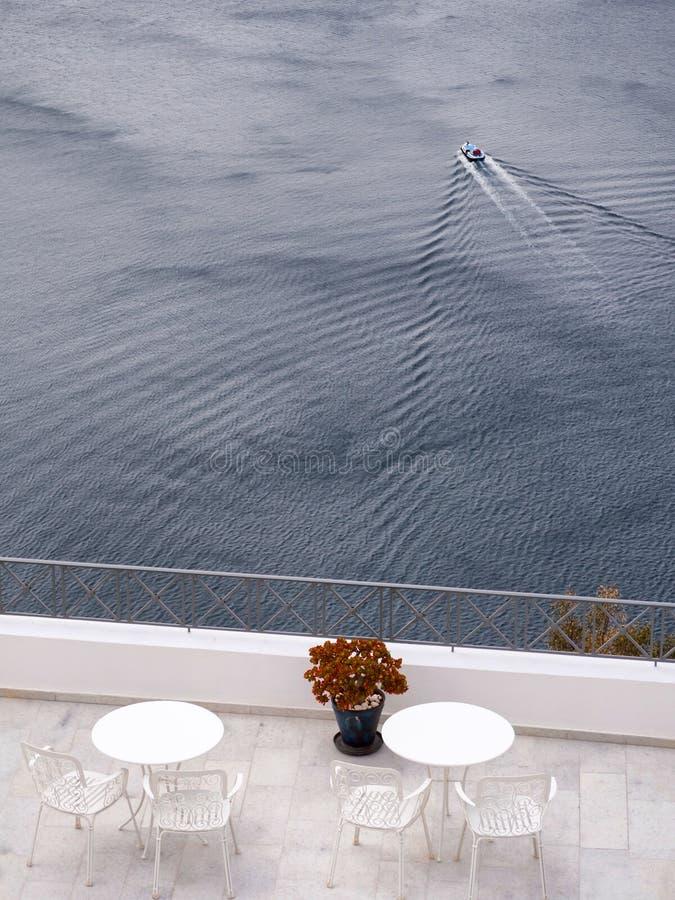 Balcone con le tavole e la bella vista del mare immagini stock