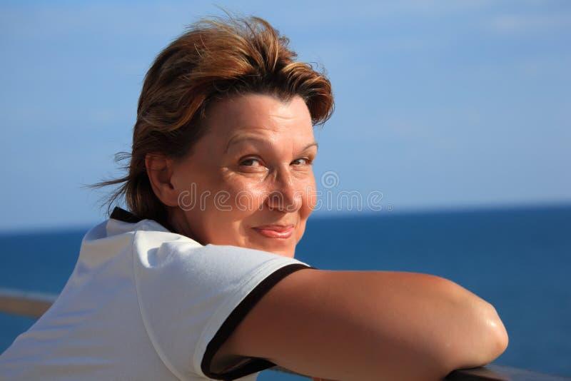 balcone di mezza età sopra la donna del mare del ritratto immagini stock libere da diritti