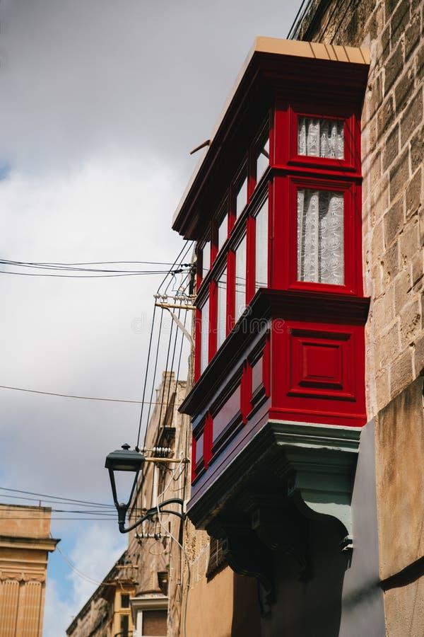 Balcone maltese rosso di legno tradizionale tipico alla via medievale stretta in Mdina, capitale antica di Malta, medievale forti fotografia stock
