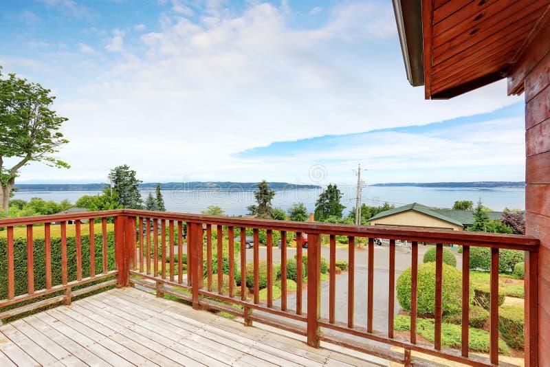 Balcone non ammobiliato e vuoto con la vista perfetta dell'acqua e le inferriate di legno immagine stock
