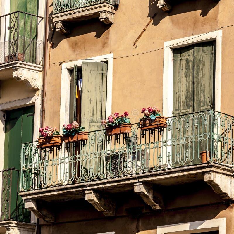 Balcone tradizionale antiquato con i fiori a Venezia, Italia fotografie stock libere da diritti